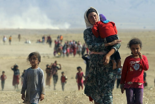 File photo of displaced people from the minority Yazidi sect, fleeing violence from forces loyal to the Islamic State in Sinjar town, walking towards the Syrian border