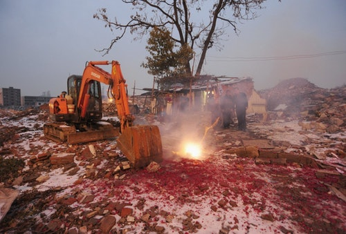 Cao Wenxia, the owner of a nail house, lights firecrackers to celebrate Chinese New Year near an excavator used for demolishing buildings near his house in Hefei
