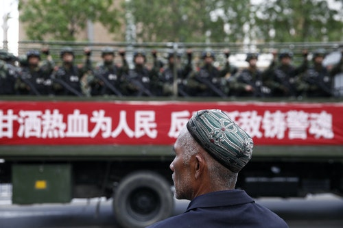 新疆_維吾爾_A Uighur man looks on as a truck carrying paramilitary policemen travel along a street during an anti-terrorism oath-taking rally in Urumqi