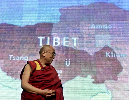Dalai Lama stands beneath map of Tibet projected on screen during public talk in Washington