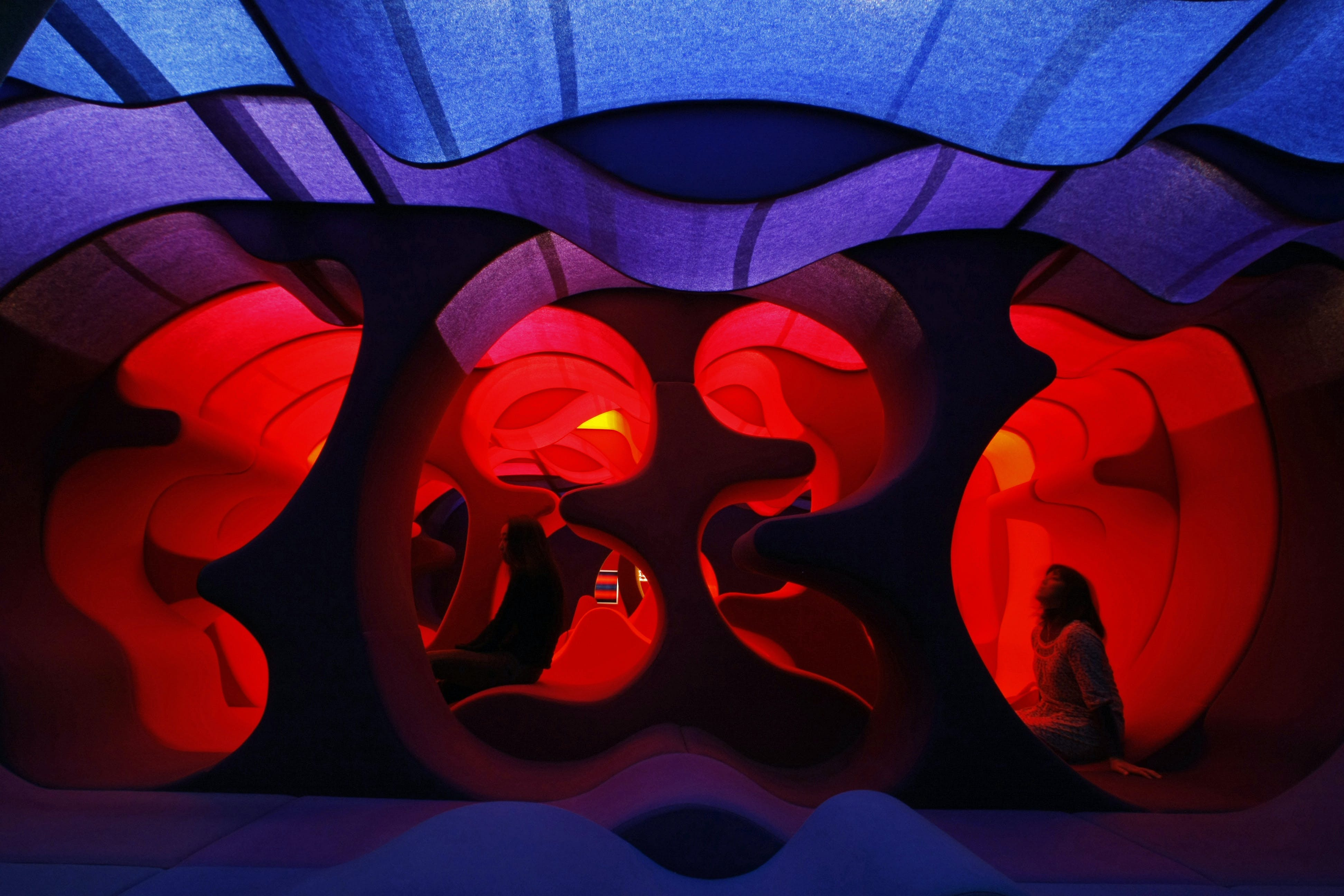 """A visitor sits on Verner Panton's """" Phantasy Landscape"""" which is made of fabric, wood and foam rubber, at the Tokyo Opera city art gallery in Tokyo"""