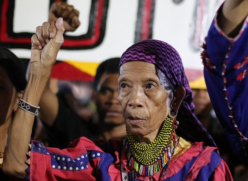 """Philippine indigenous people known as """"Lumads"""" from southern Philippines raise their clenched fists as they arrive at the Redemptorist church in suburban Baclaran, Paranaque, south of Manila, Philippines on Sunday, Oct. 25, 2015. The protesters have traveled to Manila to air their grievances against a paramilitary group and the military whom they alleged to have been behind the recent killings of """"Lumad"""" leaders and to call for a stop in the attacks against activists in southern Philippines. (AP Photo/Aaron Favila)"""