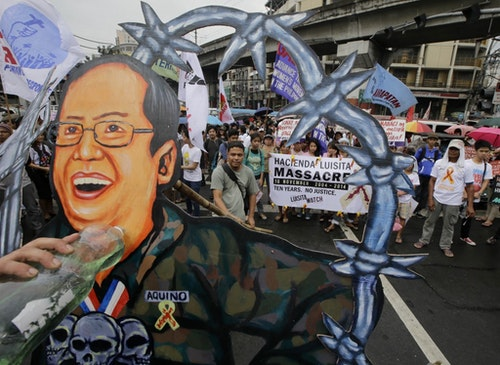 Protesters prepare to burn a cutout of Philippine President Benigno Aquino III during a rally near the Presidential Palace in Manila, Philippines Saturday, Nov.15, 2016 to mark the 10th anniversary of the killing of seven farmers and supporters at the vast sugarcane plantation owned by the family of Corazon Aquino, the late mother of the President. The protesters are demanding justice for the killings as well as the implementation of genuine land reform of the plantation known as Hacienda Luisita. (AP Photo/Bullit Marquez)