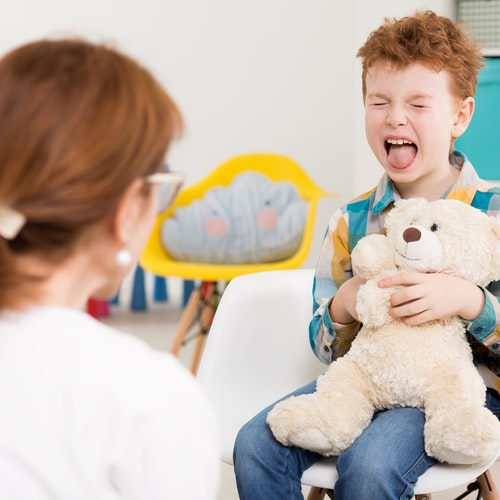 Naughty child holding teddy bear at psychologist's office