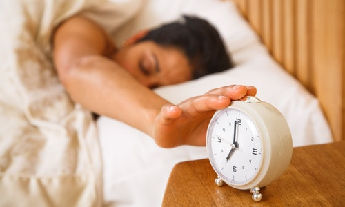 An Indian Asian woman wakes up and reaches to turn off a traditional alarm clock