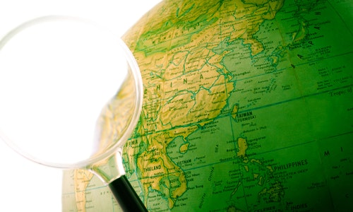 A green globe with a magnifying glass