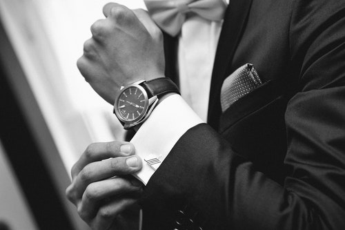 Close up of elegant man in suit with watch on hand — Photo by vladteodor95