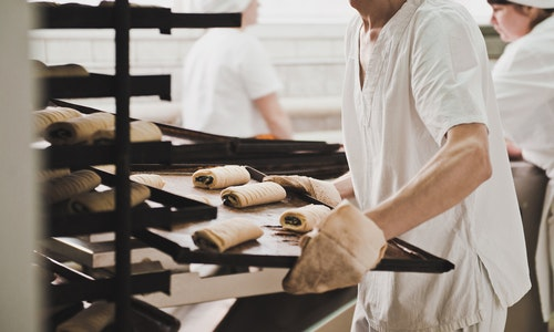 A worker carries a tray of bread. - Image
