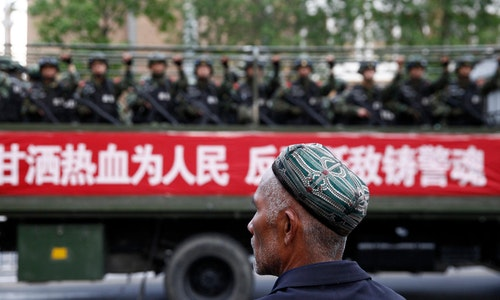 新疆_維吾爾_A_Uighur_man_looks_on_as_a_truck_